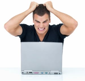 Frustrated young man using a laptop